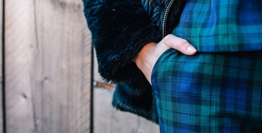 Closeup of a person leading against a boarded fence, hand in their pocket. They are dressed in plaid pants and with a matching vest or top.