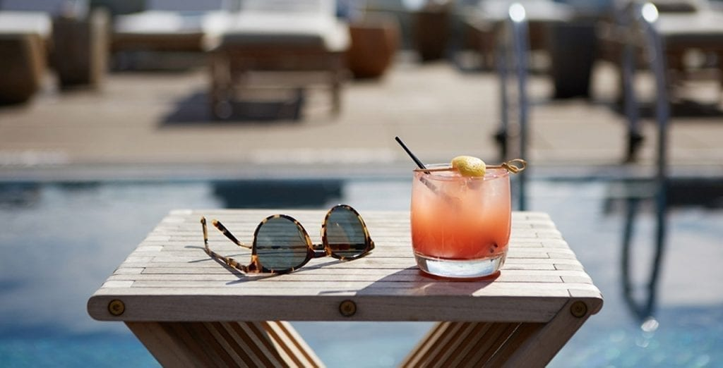 Closeup of a wooden X-frame table in the pool area of The James Hotel SoHo. A coral colored cocktail is placed next to a set of sunglasses.