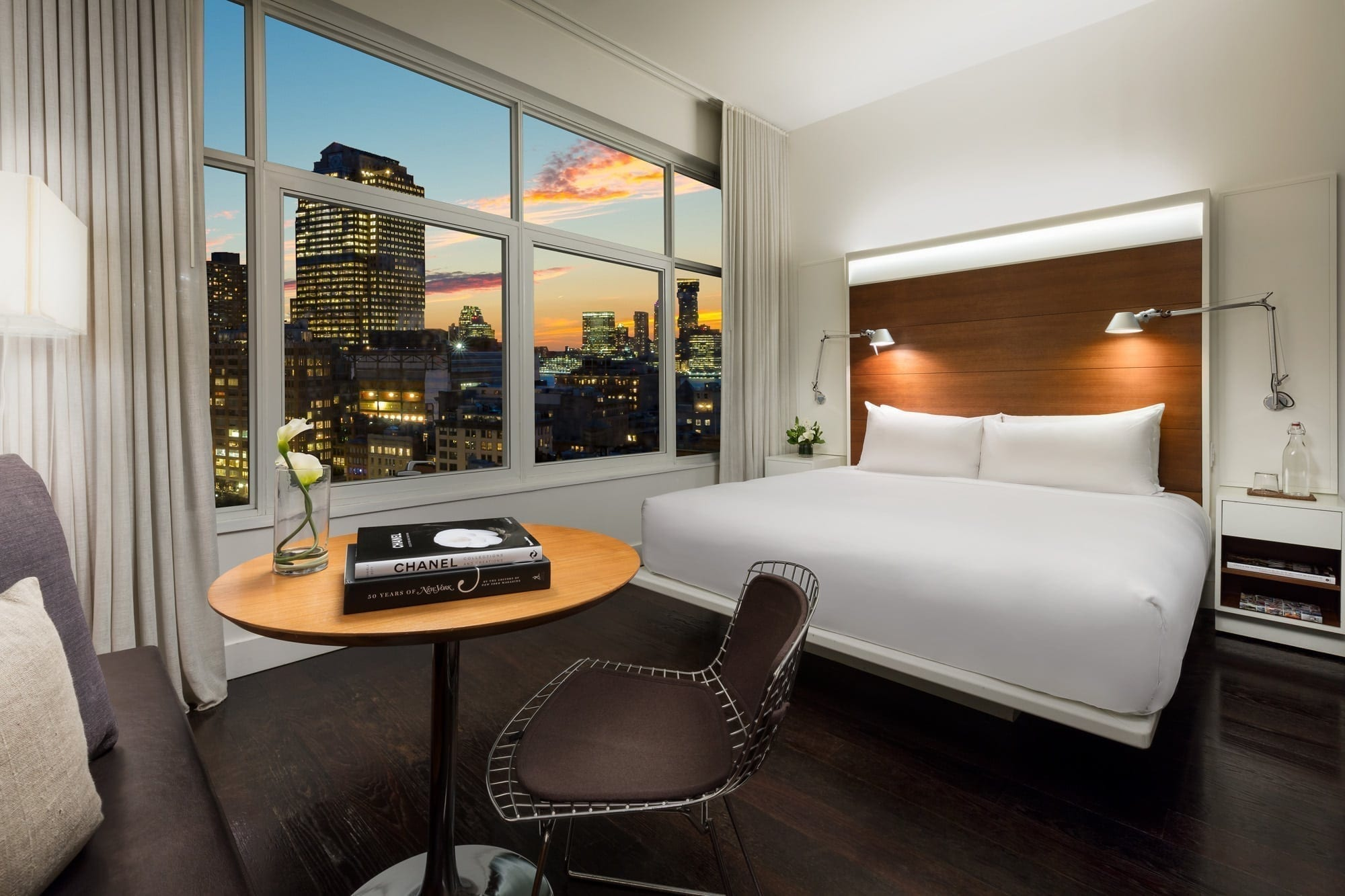 Alternate view inside a guestroom of The James Hotel SoHo. A pair of lamps lights up each side of the King sized bed. The wide window offers a generous view of the New York City skyline.