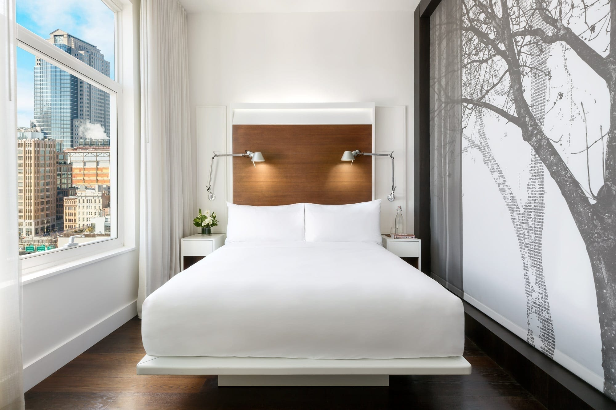 View from the foot of the queen sized bed inside a guestroom of The James Hotel SoHo. To one side is a wall panel with artwork of a tree in silhouette. At the right, there is a window looking to the city outside.