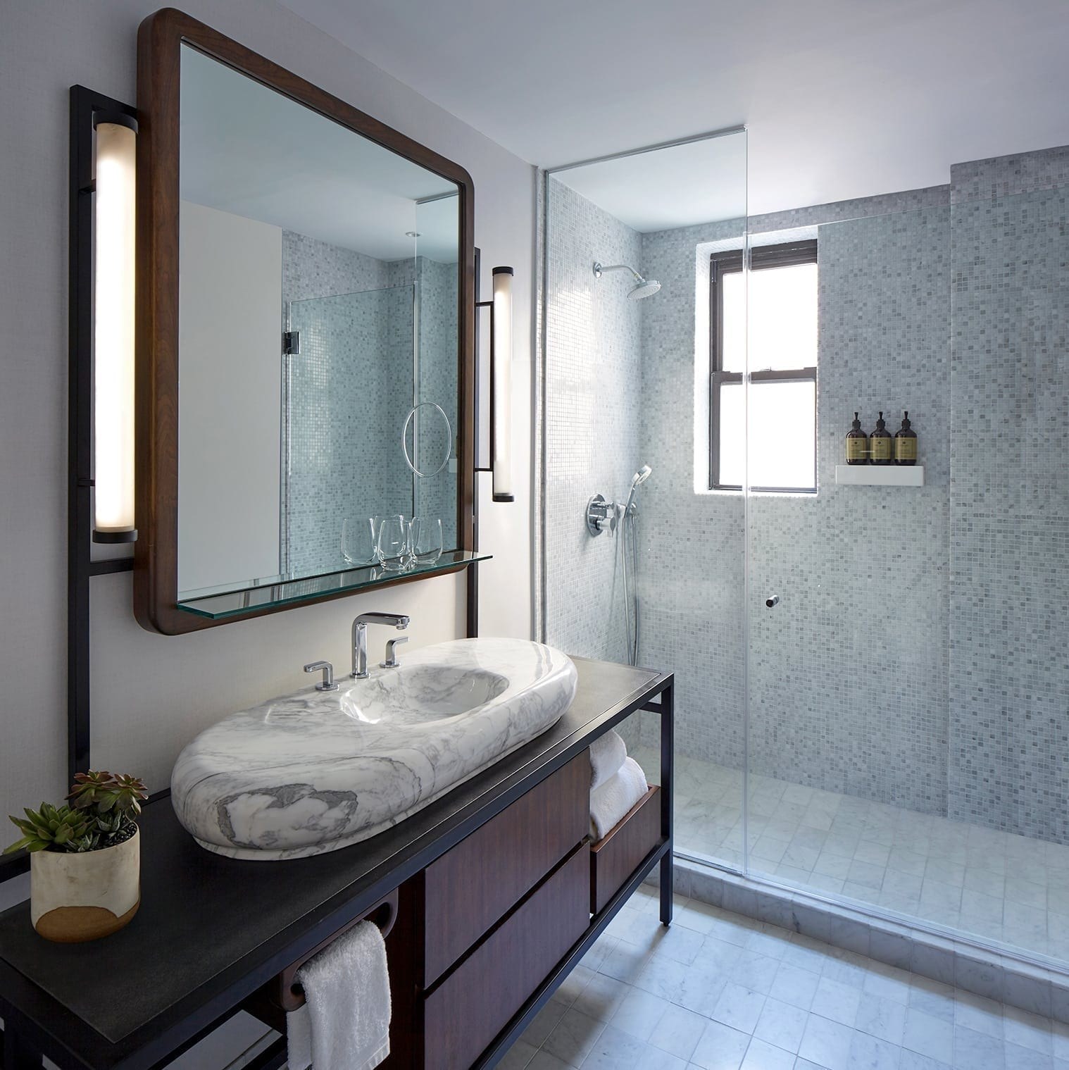 Looking inside the bathroom of the Jimmy Suite at the James Hotel (NoMad). A full sized shower chamber receives light from a window. Towels, toiletries and complementary items are stocked within the sink and cabinet.