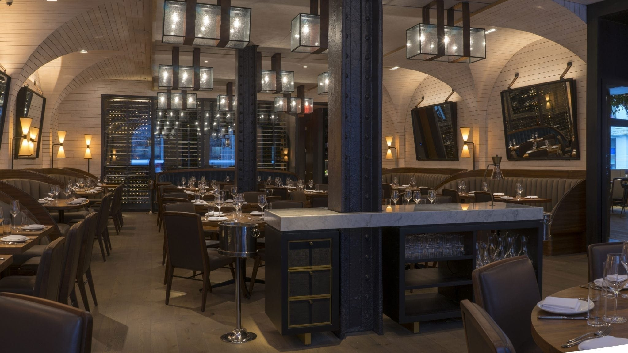 Prepared dining area inside Scarpetta. Lighting has been dimmed and set to give a warm glow.