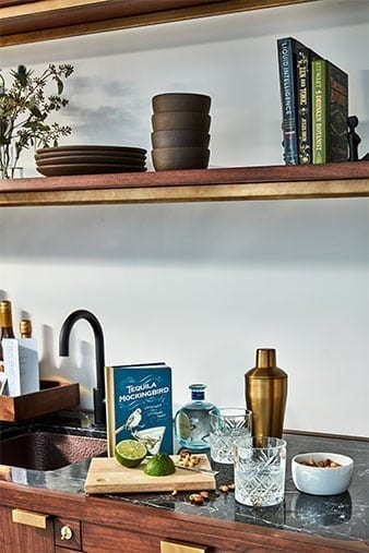 Kitchen counter of The James Hotel NoMad's Penthouse Suite. A cutting board has been set down next to a bowl. Two glass tumblers lay empty and a book is placed upright in the back.