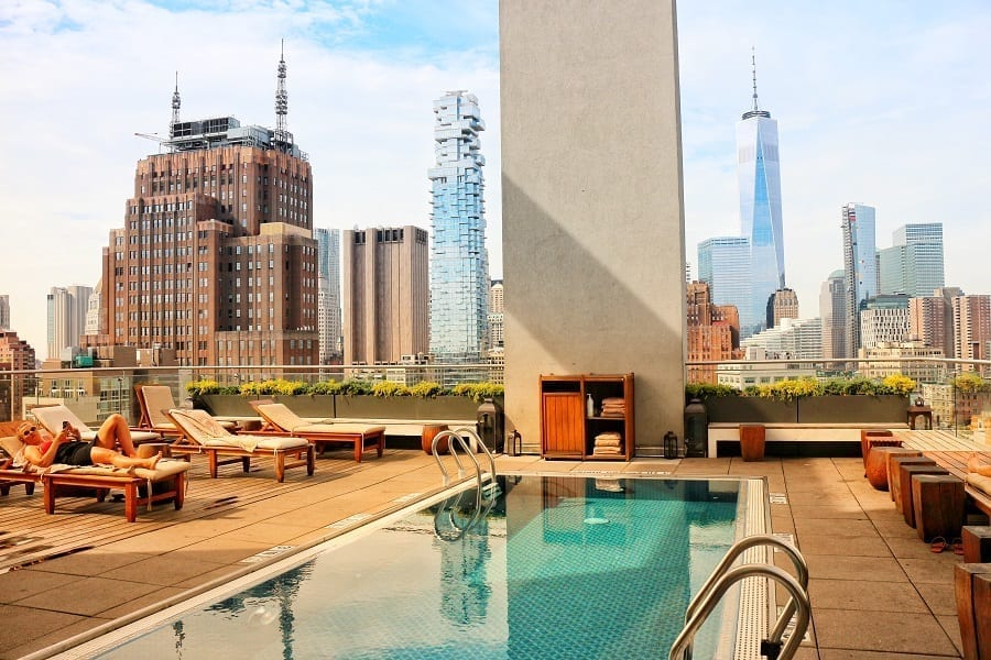 View of high rise apartments and landmarks from the rooftop pool of The James SoHo. The pool water is undisturbed, in the shade. A guest can be seen lounging in one of the chairs places around the pool.